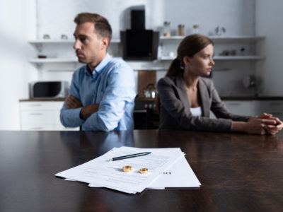 selective focus of couple sitting at table with divorce documents about to call abbott law office