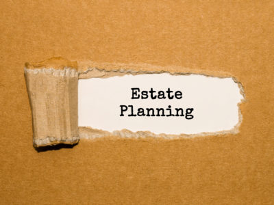 The text Estate Planning appearing behind torn brown paper