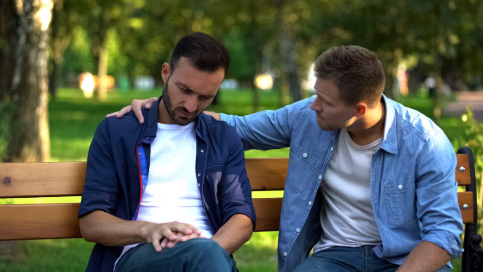 Young male supporting divorced friend sitting outdoors together, friendship care, advice